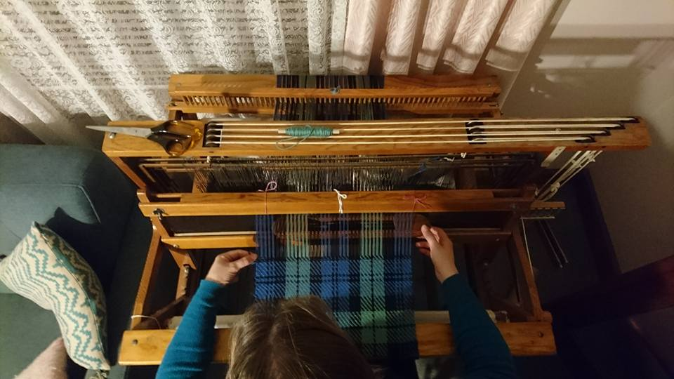 View from above of Emilt weaving blue/green/black twill on a four-shaft table loom using a boat shuttle.