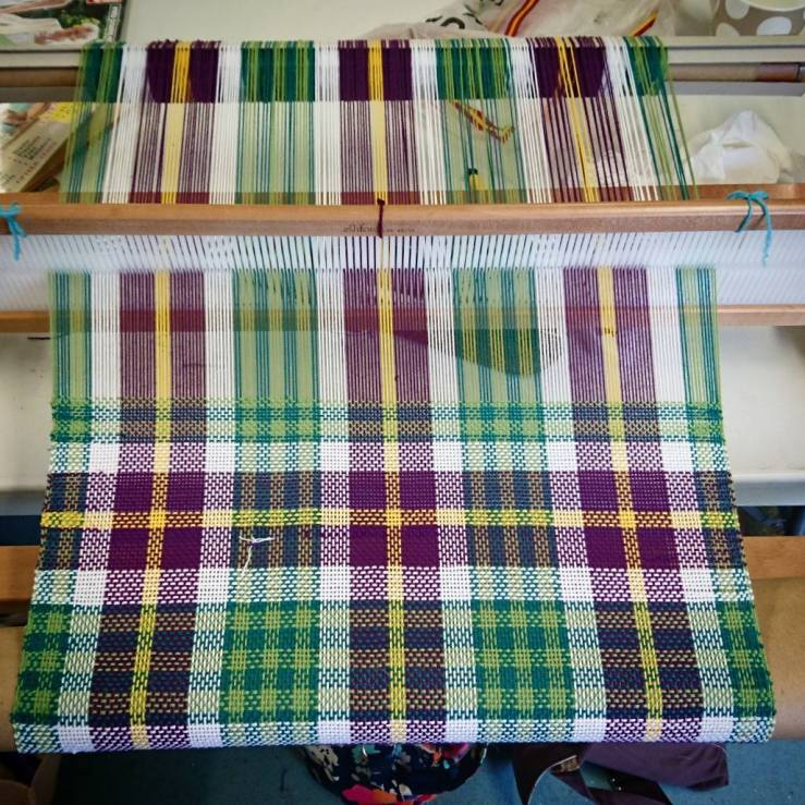 weaving on a rigid heddle loom - a checked / plaid pattern of light green, dark green, white, purple and gold.