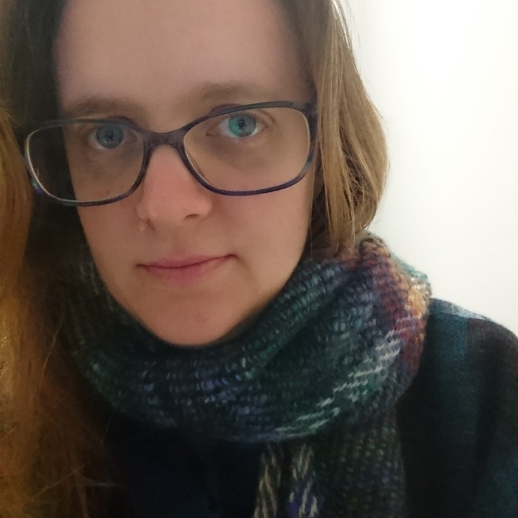 Profile image - Emily A close-up view of a woman with light skin, blue eyes and brown hair wearing glasses and a multi-coloured scarf