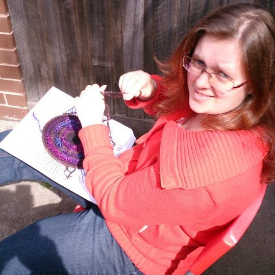 A woman sitting outside in the sun holding yarn and a square of cardboard. The cardboard has a circle of woven yarn in the centre of it.