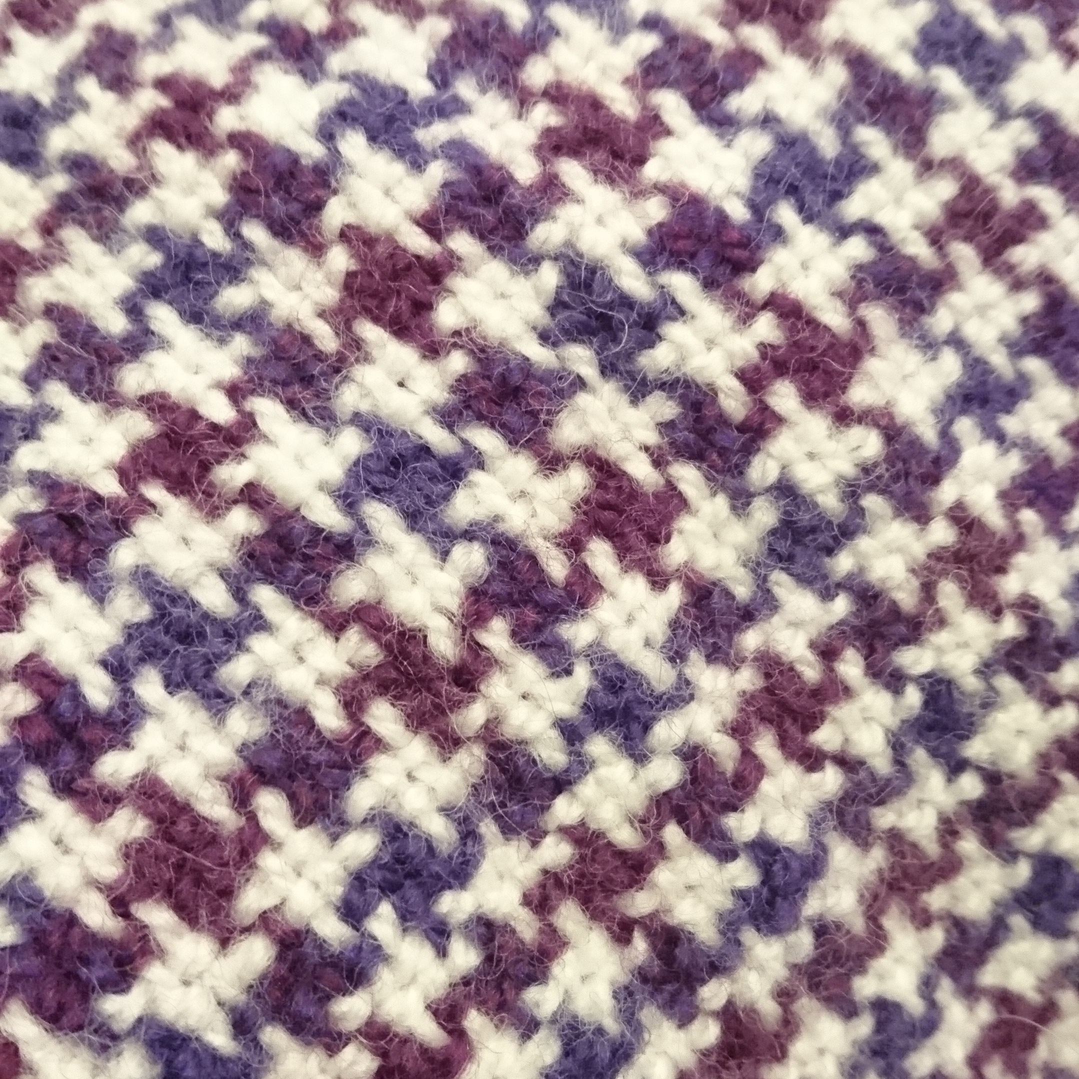 Weaving featuring small checked / criss-crosses of white, plum and purple in a houndstooth pattern.