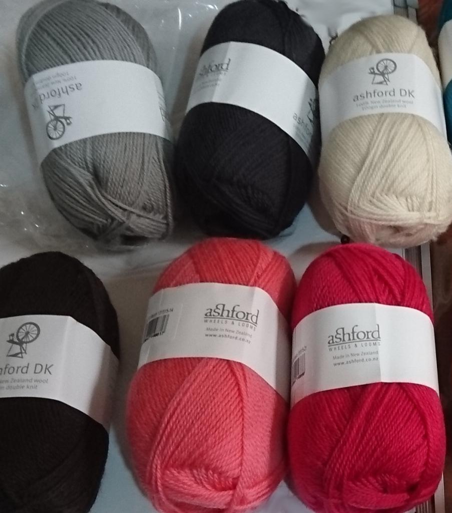 6 balls of Ashford DK wool yarn, from top left: smoke (light grey), granite (dark grey), natural white, chocolate (dark brown), coral (light pink) and rogue (dark pink.