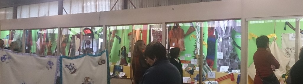 A wall of glass display cases, filled with handmade woollen items, people are standing in front of the glass looking thoughtfully at the exhibits.