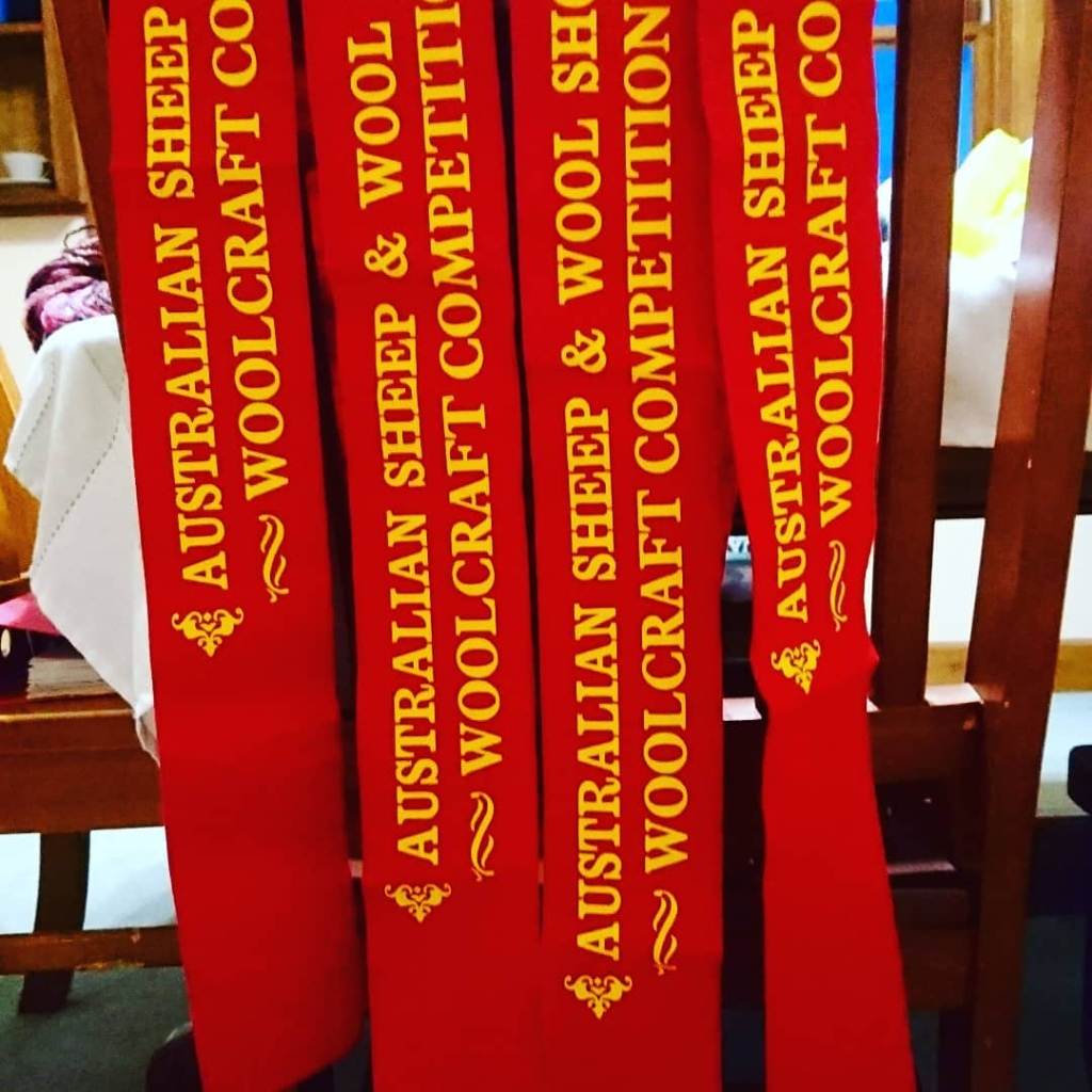 """Four red felt sashes/ribbons hanging from the back of a timber chair. Yellow print on the ribbons says """"AUSTRALIAN SHEEP & WOOL SHOW WOOLCRAFT COMPETITION"""""""
