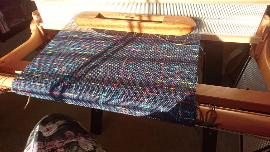 Rigid heddle loom with weaving in progress, with bright sunlight shining on the surface of the weaving. The yarn in both warp and weft is dark blue with random short stripes of green, yellow, pink, light blue and orange. The stripes intersect each other at right angles like an abstract geometric or grid pattern.