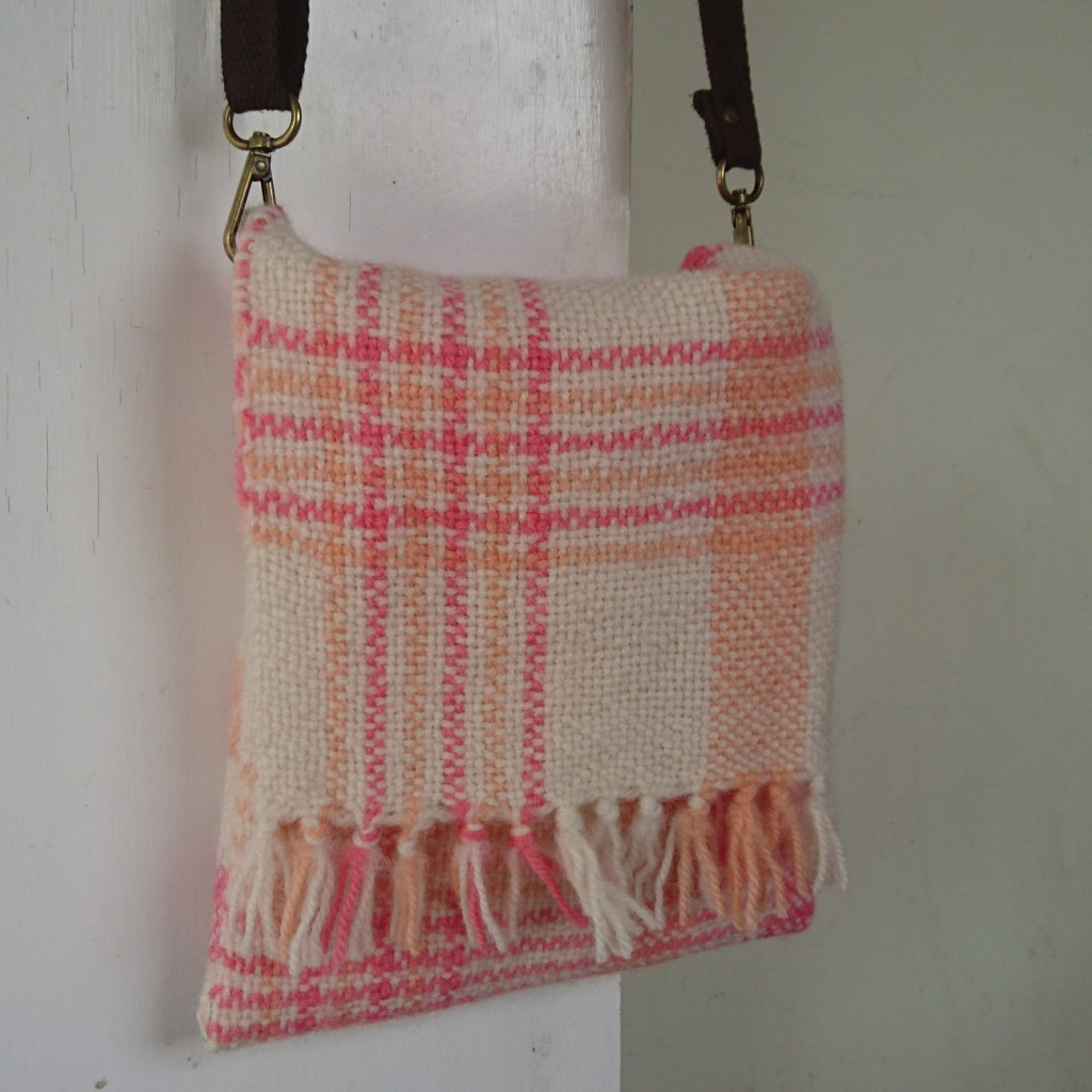 Small square messenger / satchel bag made of woven cloth in white with peach and pink stripes and checks, with a short fringe in the front flap. It's hanging from a brown strap with metal clips on a white door