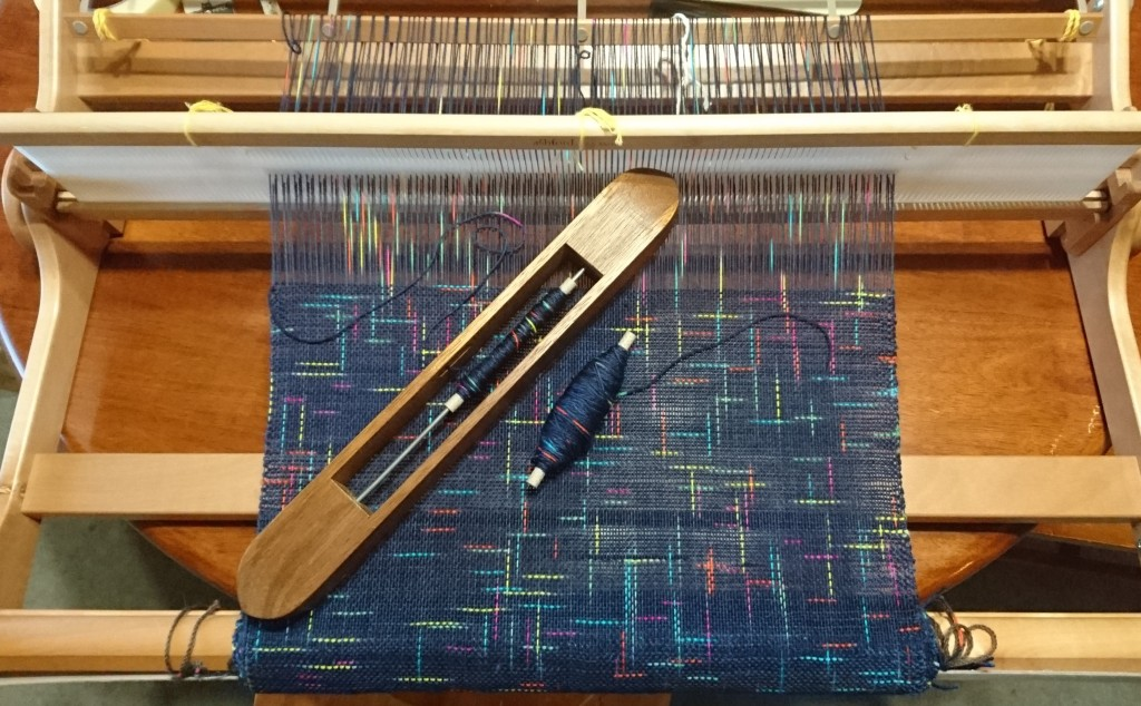 A rigid heddle loom on a wooden table with weaving in progress - using a yarn that is dark navy with short dashes of bright colours (pink, blue, yellow, green, orange). The coloured dashes criss-cross across the fabric. A boat shuttle is resting on top of the weaving.