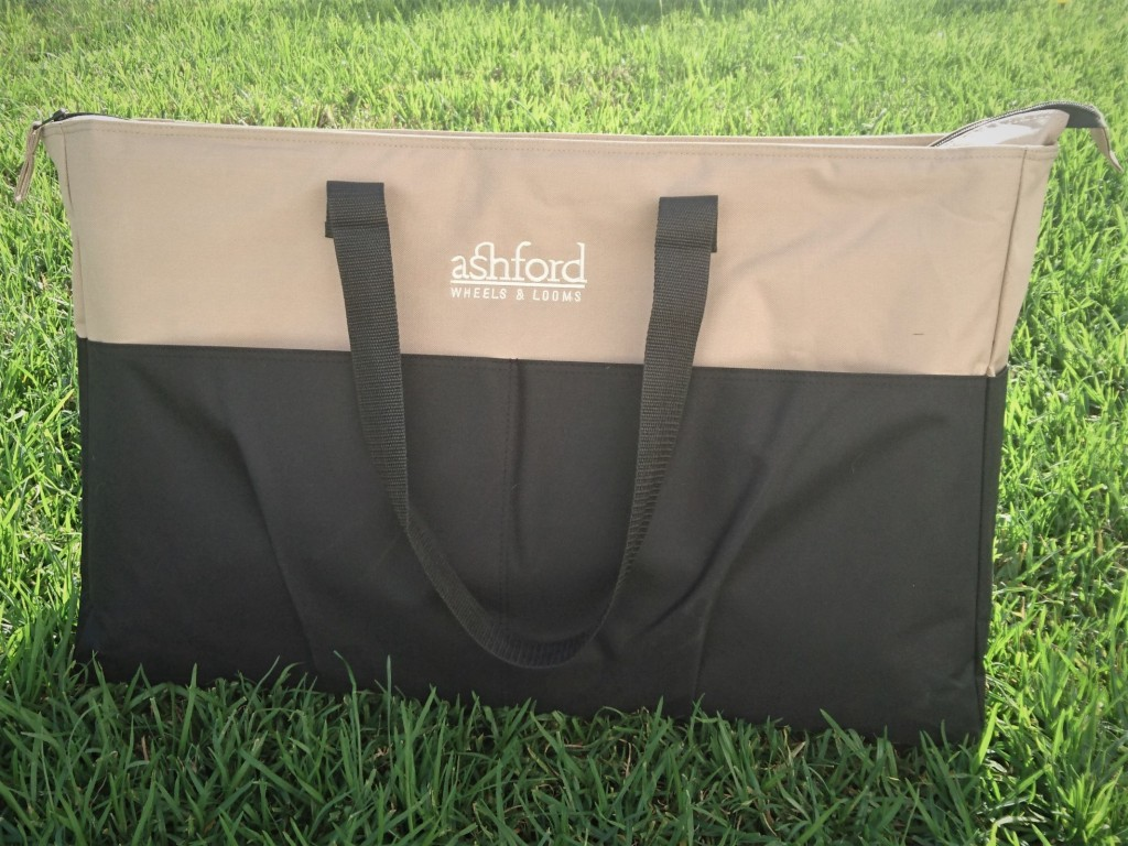 Large beige and black bag sitting on the grass, with a black carry strap and the words Ashford Wheels & Looms embroidered on in white.