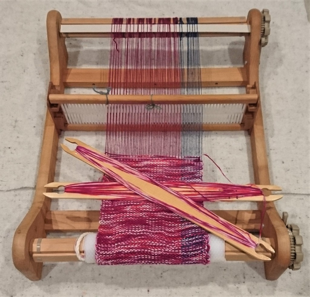 Rigid Heddle loom sitting on white fabric with a raspberry and blue warp and variegated pink & white weft. Two stick shuttles rest on the weaving.