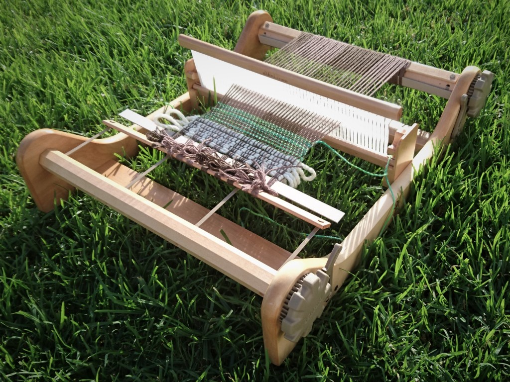 Rigid Heddle loom sitting on green grass. There is a brown warp on the loom with a little bit of white and green yarn just started weaving.