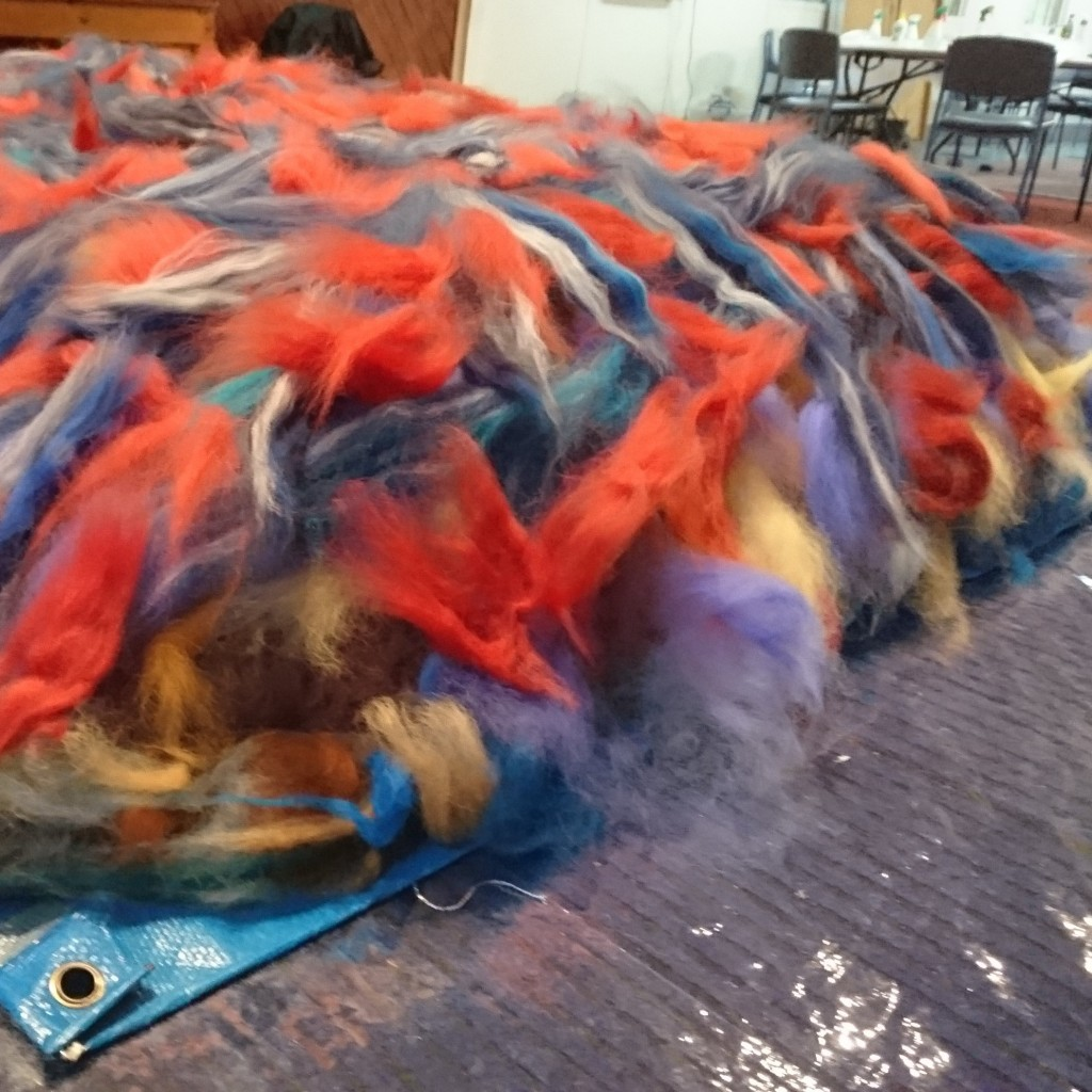 a large pile of fluffy tufts of fibre (wool, alpaca, silk, flax etc) in many colours, spread out over a blue tarp and plastic covers, there are lots of chairs & tables in the background.