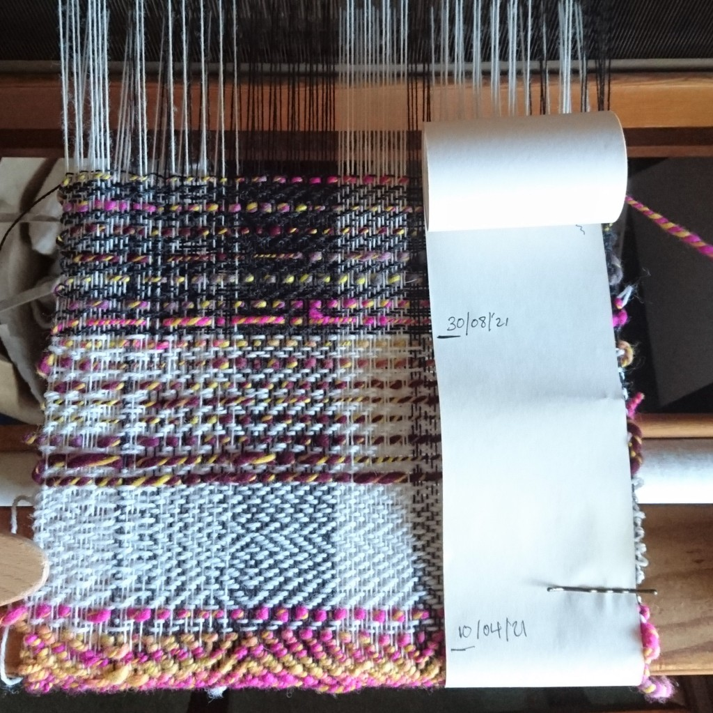 Weaving on a loom in a mix of twill patterns using grey, white thin yarns and a thick variegated handspun yarn in yellow, pink & purple. A long thing roll of paper is attached to one side with bobby pins recording the dates of weaving, it jumps from 10/04/21 to 30/08/21.